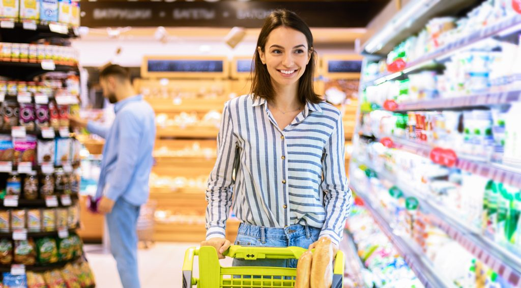 Woman in grocery store pushing cart full of food.
